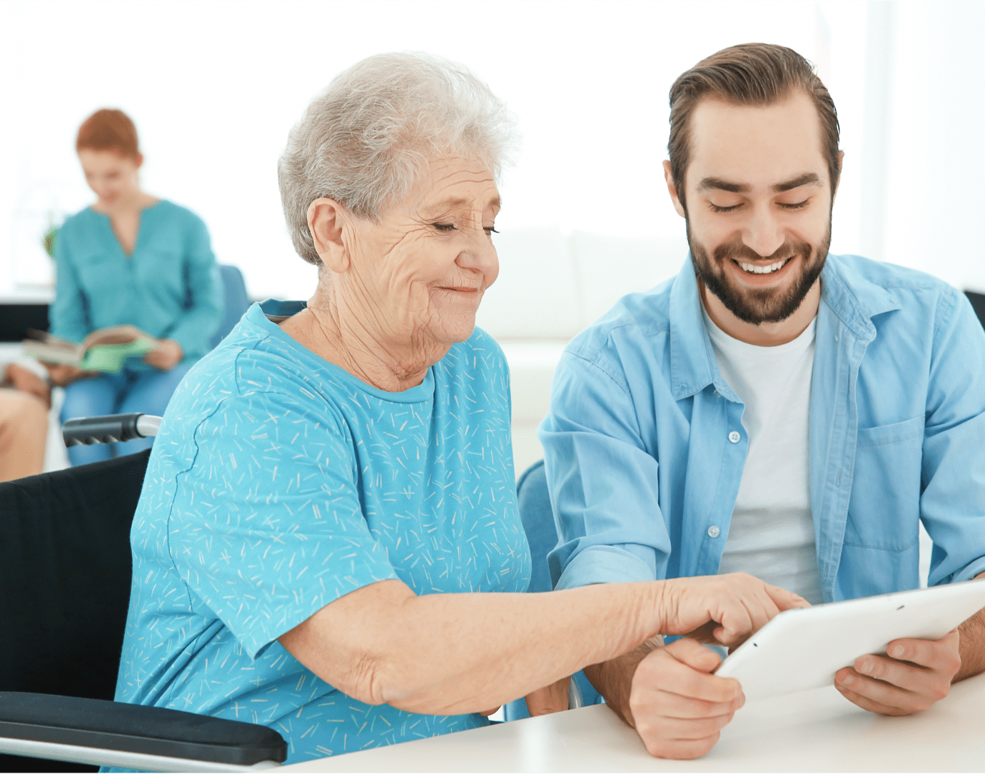 Older woman using tablet with younger man
